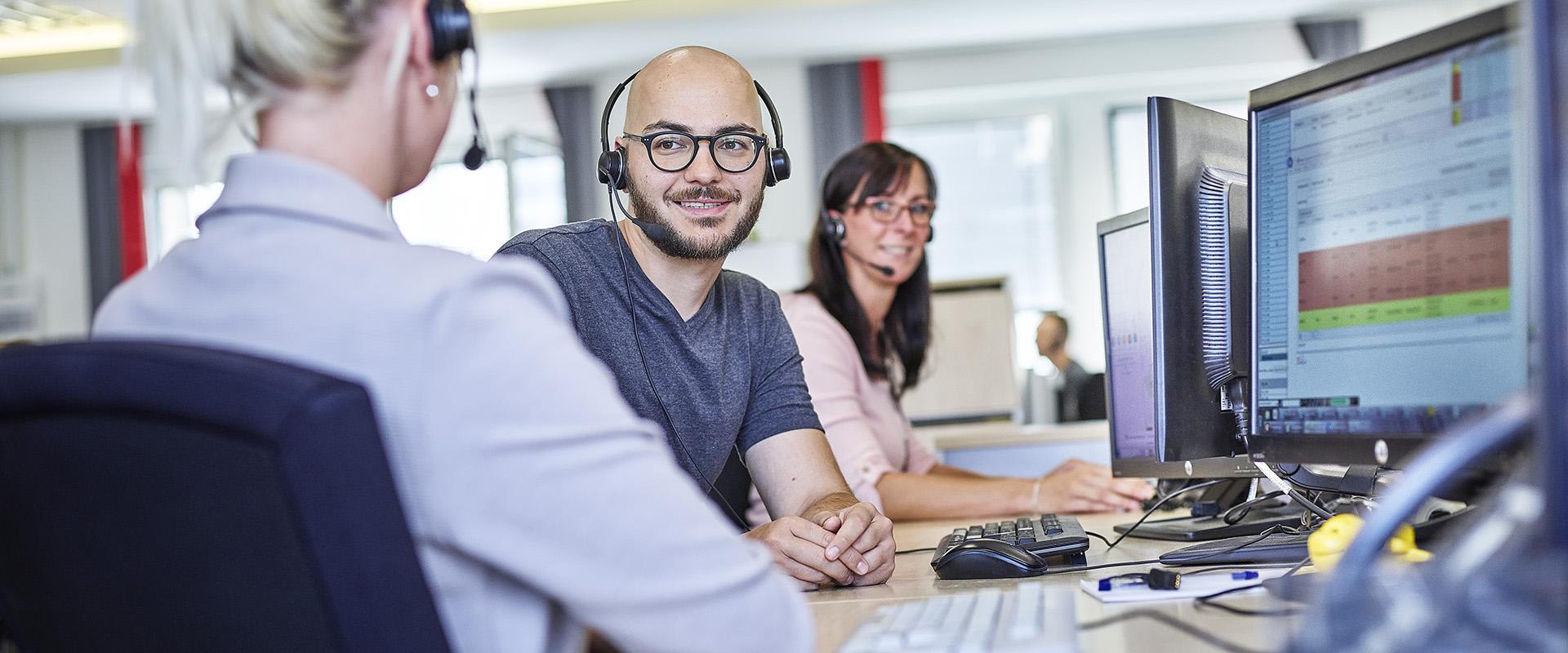 Mitarbeiter mit Headset am Arbeitsplatz